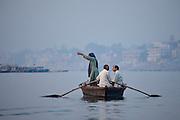 Traditional scene on River Ganges Hindu pilgrim pours Ganges water while praying at Varanasi, Benares, Northern India