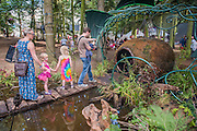 Children are intrigued by a moss covered ball that is reached accross a pond and climbed into (in the Solas healing area) - The 2016 Latitude Festival, Henham Park, Suffolk.