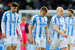 Huddersfield Town's Jonathan Hogg (centre) and Huddersfield Town's Aaron Mooy (right) leave the pitch dejected at half time during the Premier League match at the John Smith's Stadium, Huddersfield.