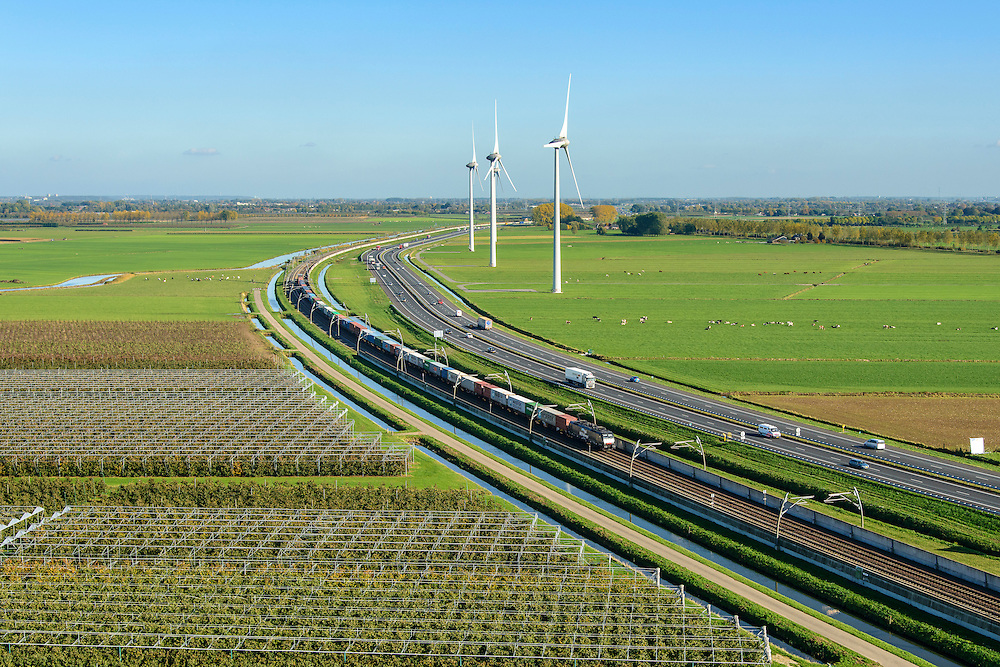 Nederland, Gelderland, Betuwe, 24-10-2013; Betuweroute, ter hoogte van Echteld. De goederenspoorlijn loopt parallel aan autosnelweg A15. De goederentrein is onderweg naar de haven van Rotterdam. Boomkwekerijen links onder in beeld, daarachter de rivier de Linge.<br />