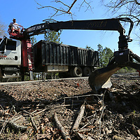 Thomas Wells   BUY at PHOTOS.DJOURNAL.COM<br /> Tupelo Public Works employee Cody McMurry removes piles of debris along the road in West Tupelo on Tuesday.