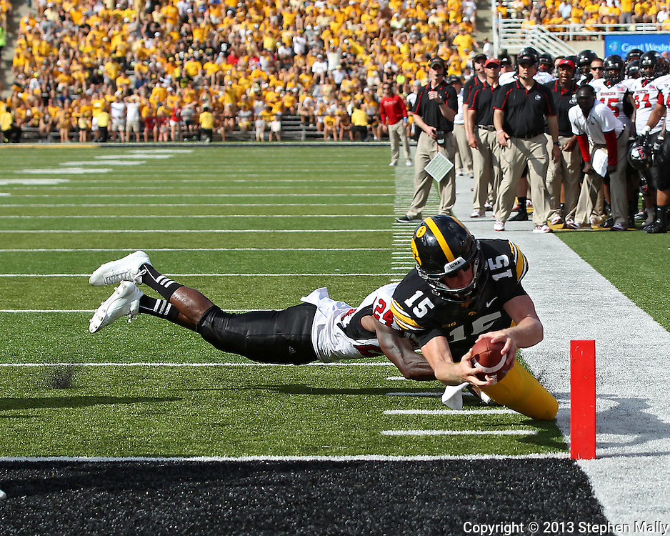 August 31 2013: Iowa Hawkeyes quarterback Jake Rudock (15) dives for the end zone on a 6 yard touchdown run during the second quarter of the NCAA football game between the Northern Illinois Huskies and the Iowa Hawkeyes at Kinnick Stadium in Iowa City, Iowa on August 31, 2013. Northern Illinois defeated Iowa 30-27.