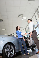 Car salesman shaking hands with female customer in showroom