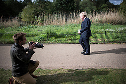 © Licensed to London News Pictures. 11/05/2020. London, UK. A photographer kneels to take a picture as British Prime Minister BORIS JOHNSON is seen walking in St James's Park near Downing Street in Westminster, London. Government has announced a series of measures to slowly ease lockdown, which was introduced to fight the spread of the COVID-19 strain of coronavirus. Photo credit: Ben Cawthra/LNP