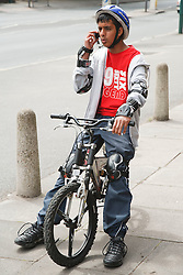 Asian teenager sitting on a bike and talking on  his mobile phone.