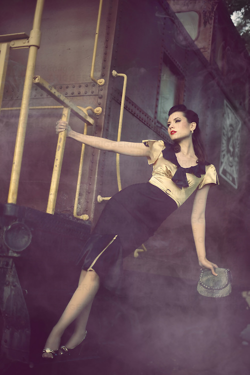 A young vintage 1940s pinup hangs off the side of a smoky train.