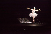 A male dancer from Les Ballets Trockadero de Monte Carlo spoofs Fokine's Dying Swan, a role first played by Anna Pavlova in 1905. Feather's fall from his costume as rain starts to fall, and the sudience raises umbrellas, as seen in the shadow on the left.