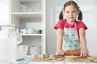 Girl (5-6) rolling dough in kitchen portrait