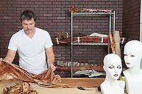 Mature male fashion designer working on cloth in design studio