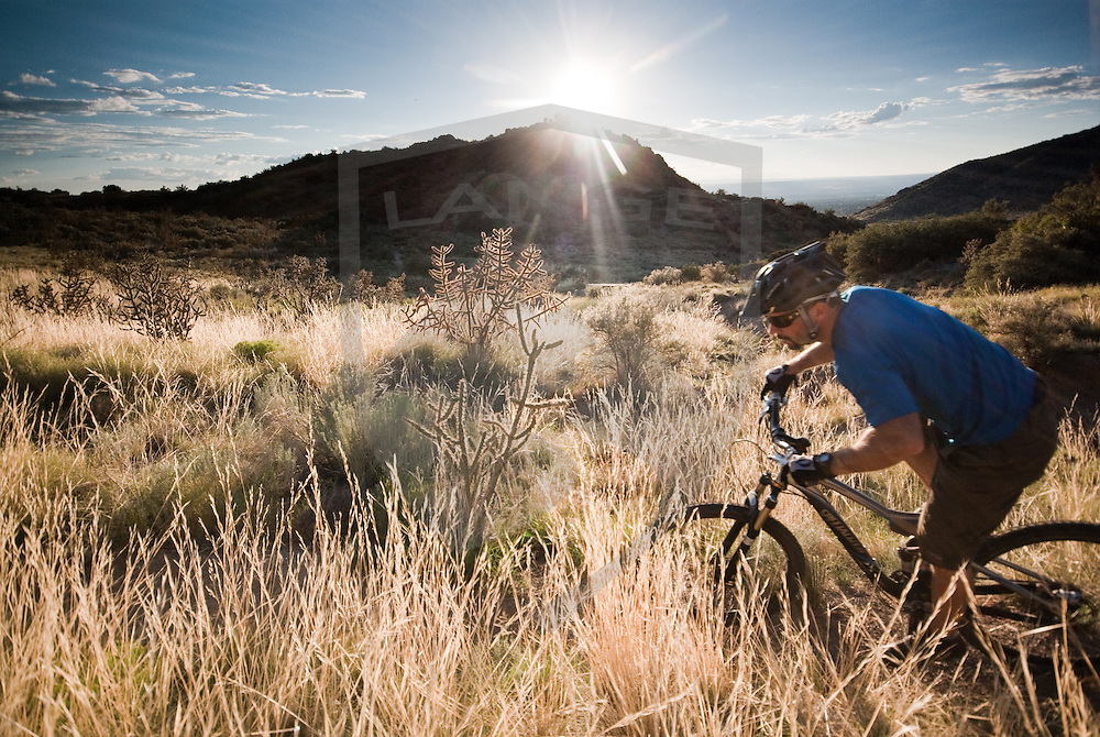 mountain bike rider kevin lange cycles across the desert mountain terrain of the sandia mountains foothill trail system near albuquerque, new mexico.