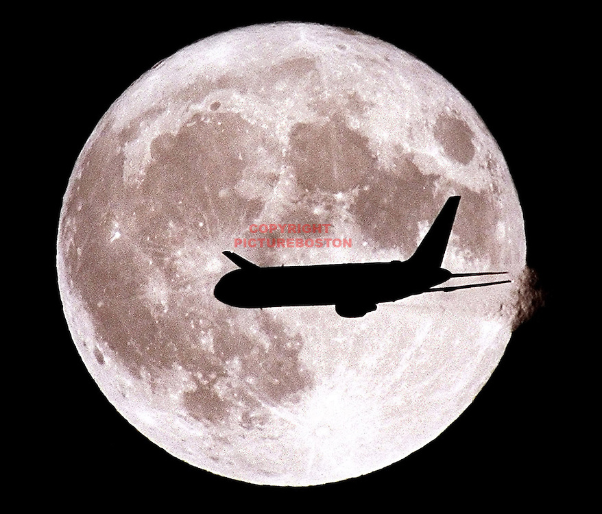 "An evening departure off of a Logan International Airport runway passes ""through"" the moon....."