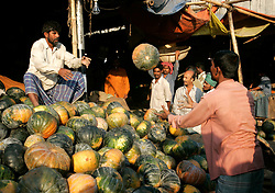 BANGLADESH DHAKA KAWRAN BAZAAR 27FEB05 - Pumpkin traders at work at the Kawran Bazaar vegetable market. The Bazaar has been in the Tejgaon area for at least 30 years and is one of the largest markets in Dhaka city...jre/Photo by Jiri Rezac ..© Jiri Rezac 2005..Contact: +44 (0) 7050 110 417.Mobile:  +44 (0) 7801 337 683.Office:  +44 (0) 20 8968 9635..Email:   jiri@jirirezac.com.Web:    www.jirirezac.com..© All images Jiri Rezac 2005- All rights reserved.