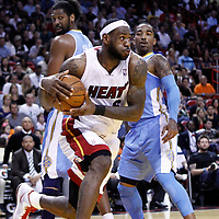 19 March 2011: Miami Heat small forward LeBron James (6) drives past Denver Nuggets center Nene Hilario (31) and Denver Nuggets shooting guard J.R. Smith (5) during the Miami Heat 103-98 victory over the Denver Nuggets at the AmericanAirlines Arena, Miami, Florida, USA.