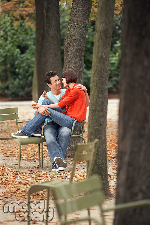 Couple eating snack sitting on chairs in park
