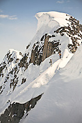 Two women prepare to ski steep couloir in the Perfect Valley, outside of the Sorcerer's Lodge, on a backcountry ski touring hut trip in British Columbia, Canada.