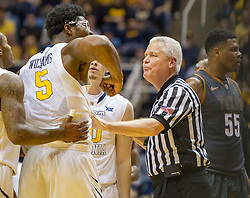 West Virginia Mountaineers forward Devin Williams (5) is held back by a referee against the Texas Longhorns during the first half at the WVU Coliseum.