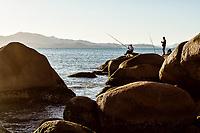 Homens pescando sobre pedras na Praia de Ponta das Canas. Florianópolis, Santa Catarina, Brasil. / Men fishing on rocks at Ponta das Canas Beach. Florianopolis, Santa Catarina, Brazil.