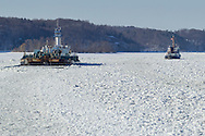 The United States Coast Guard cutter Thunder Bay, at right, breaks ice in the shipping channel on the Hudson River near Hudson, New York. The Eva Leigh Cutler, an oil tank barge, is at left,