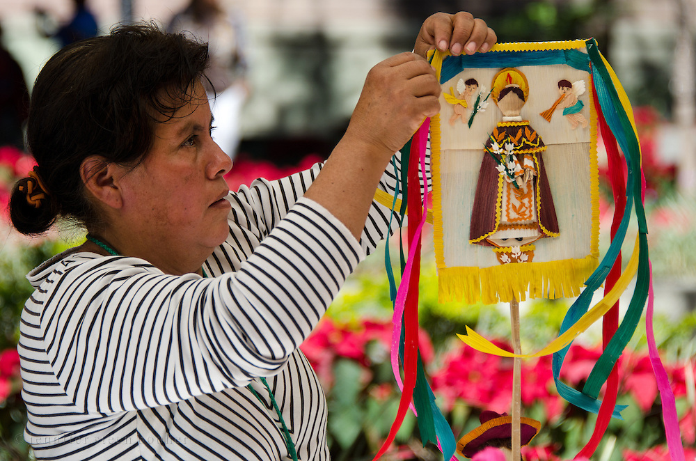 Woman assembling a processional banner made of totomoxtle, or corn husks, for the Noche de Rabanos festival, Oaxaca, Mexico.