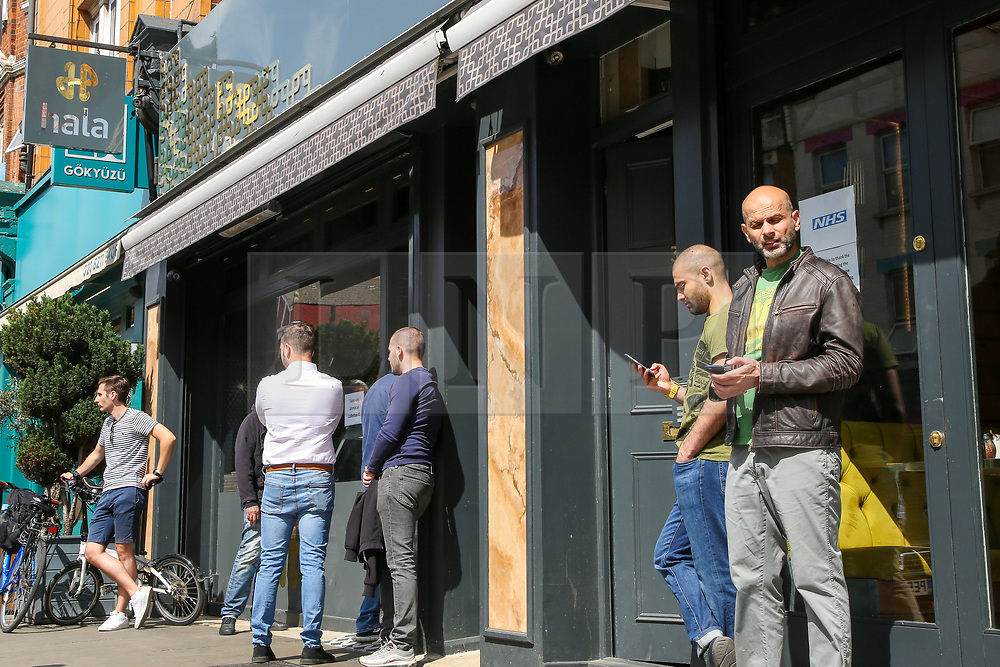 """© Licensed to London News Pictures. 24/05/2020. London, UK. People queue outside 'HALA' Turkish restaurant on Green Lanes, Haringey in north London which is open for take away only due to coronavirus lockdown, as Muslims celebrate Eid al-Fitr.  On Eid al-Fitr also known as """"Festival of Breaking the Fast"""", a religious holiday celebrated by Muslims worldwide that marks the end of the month-long fasting of Ramadan, restaurants would normally be packed with people celebrating Eid. Photo credit: Dinendra Haria/LNP"""
