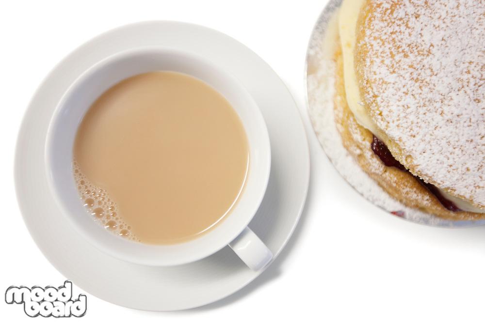 High angle view of tea cup and powdered sugar cake slice
