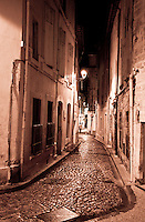 Atmospheric night shot of a narrow winding alleyway in Avignon, France at night.
