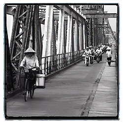 View of the long bien bridge's metallic structure in Hanoi. A woman rides a bicycle with a conic hat and carries two buckets. In the background, a woman walks and carries a yoke. Bridge crowded of motorbikes.
