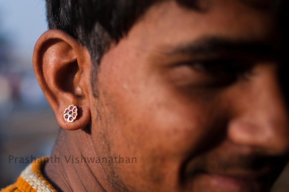 A man sports a traditional ear ring at the fair grounds in Pushkar, India, November 6, 2011.  Photographer: Prashanth Vishwanathan