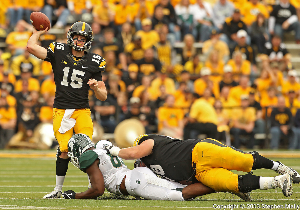 October 6 2013: Iowa Hawkeyes quarterback Jake Rudock (15) is hit by Michigan State Spartans defensive end Shilique Calhoun (89) as Iowa Hawkeyes offensive linesman Brandon Scherff (68) tries to hold him back during the second half of the NCAA football game between the Michigan State Spartans and the Iowa Hawkeyes at Kinnick Stadium in Iowa City, Iowa on October 6, 2013. Michigan State defeated Iowa 26-14.
