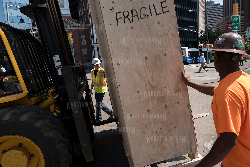 "May 26, 2015 - New York, NY : Four fiberglass fish are delivered to Seaglass Carousel in large crates, in Battery Park on Tuesday morning, May 26. Here, Cedric Revest of Show Canada Inc., left, and Ancell Brown of NY Local 580, foreground right, help steady a crate containing a fish as it is moved by forklift. A project of The Battery Conservancy, the Seaglass Carousel, which is set to open in mid-July, is a creation of WXY Architecture and George Tsypin Opera Factory. The carousel will feature thirty fiberglass fish ranging in height from 13'7"" to 3'9"". CREDIT: Karsten Moran for The New York Times"