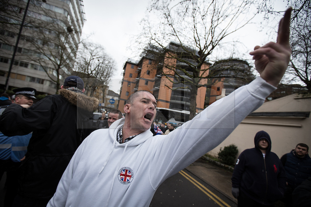 """© Licensed to London News Pictures . 04/01/2014 . London , UK . An EVF supporter gives a two-fingered salute to the mosque . A demonstration by far right groups including the English Defence League , English Volunteer Force, New British Union and English Nationalist Alliance against a planned anti-gambling demonstration by """" The Sharia Project """" outside the Regents Park Mosque in London today (4th January 2014) . The Sharia Project opposes democracy and wish for a global caliphate governed by Sharia law . Photo credit : Joel Goodman/LNP"""