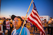 "23 JUNE 2012 - PHOENIX, AZ:  An opponent of Maricopa County Sheriff Joe Arpaio waves an American flag during a protest against the Sheriff in front of the county jails Saturday. About 2,000 members of the Unitarian Universalist Church, in Phoenix for their national convention, picketed the entrances to the Maricopa County Jail and ""Tent City"" Saturday night. They were opposed to the treatment of prisoners in the jail, many of whom are not convicted and are awaiting trial, and Maricopa County Sheriff Joe Arpaio's stand on illegal immigration. The protesters carried candles and sang hymns.     PHOTO BY JACK KURTZ"