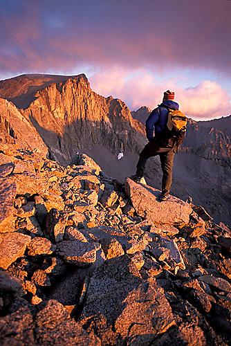 Man hiking at dawn over talus on Split Mountain in the John Muir Wilderness, CA.