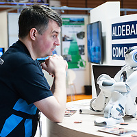 Lyon, France - 19 March 2014: an Aldebaran engineer interacts with NAO Robot  at Innorobo 2014, the 4th international trade show on service robotics.
