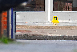 © Licensed to London News Pictures. 03/02/2020. London, UK. Evidence markers are placed on the ground next to a blood stain (L) outside Boots where the assailant was shot in Streatham High Road the day after he stabbed two people. Sudesh Amman, who was released from prison recently for terror offences, was under active police surveillance at the time of the attack - which police think was an Islamist-related terrorist incident. Photo credit: Peter Macdiarmid/LNP