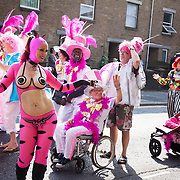 Hackney carnival 2014. The procession started in Ridley Road and passed by the The Hackney Town Hall with thousands of spectators lining the road.<br /> A group of dancers in white and pink, a woman dressed as a cat with bare breasts.