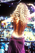 Woman with a naked back and blonde, curly hair dancing in a club, Ibiza, 1999, Model Released