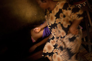 """Herbalist Cecilia Osakwe, 50, rubs the belly of a female client, in the Ajegunle neighborhood of Lagos, Nigeria, August 27, 2013.  Cecilia explains that this is part of the treatment used when a woman wants to """"remove a pregnancy."""""""