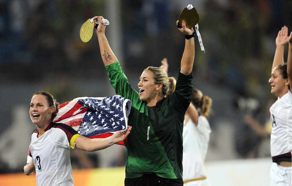 "2008 OLYMPIC GAMES - SOCCER - 082108 - USA's Hope Solo displays two ""medals"" she'd kept by her goal during the gold medal victory over Brazil. After the game, she unveiled the medals and celebrated around the field. At left is teammate Christie Rampone."
