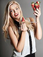 Pretty blonde girl holding glass of Strawberries