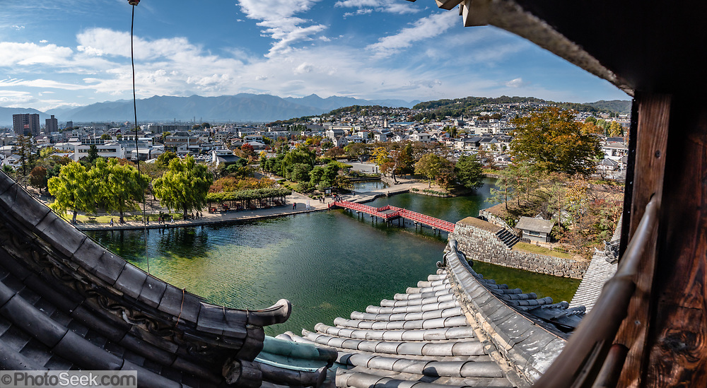 """Outward views from upper floors of Matsumoto Castle, built in 1614, in Matsumoto, Nagano Prefecture, Honshu, Japan. Matsumoto Castle is a """"hirajiro"""" - a castle built on plains rather than on a hill or mountain, in Matsumoto. Matsumotojo's main castle keep and its smaller, second donjon were built from 1592 to 1614, well-fortified as peace was not yet fully achieved at the time. In 1635, when military threats had ceased, a third, barely defended turret and another for moon viewing were added to the castle. Interesting features of the castle include steep wooden stairs, openings to drop stones onto invaders, openings for archers, as well as an observation deck at the top, sixth floor of the main keep with views over the Matsumoto city. This image was stitched from multiple overlapping photos."""