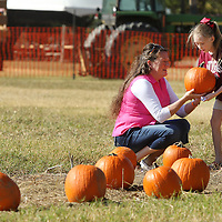 Adam Robison | BUY AT PHOTOS.DJOURNAL.COM<br /> Stacy Foster, of Corinth, hands a pumpkin to her granddaughter Kayleigh, 9, a student at Classical Conservation, as they visit the Pumpkin Patch at the Tupelo Buffalo Park and Zoo during a field trip Monday morning.