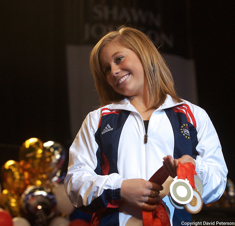 "Olympian Shawn Johnson shows off her four medals from the Beijing games Tuesday at a homecoming in Des Moines, Iowa.  Johnson's homecoming was attended by over 7,000 fans who filled the Wells Fargo Arena in Des Moines.   Included was a gold for the balance beam.  The city of Des Moines declared the month of September ""Shawn Johnson Month"".  As one of the most recognizable faces of the Beijing Olympics, Johnson has been on a whirlwind post Olympics tour, which has included an appearance on The David Letterman Show.  She will also appear on Jay Leno, and will lead the Pledge of Allegiance at this year's Democratic Convention."