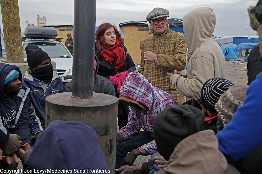 Writer AA Gill (C) and translator Bana Mina (L) talk with refugees from Darfur, Sudan, in the refugee camp in Calais France. <br />