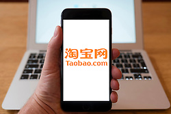 Using iPhone smartphone to display logo of Taobao Chinese online shopping and e commerce store
