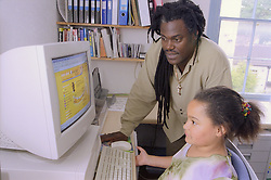 Single father teaching young daughter to use computer,