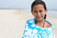 Pre-teen girl Wrapped in a Towel standing on beach