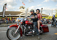 Darryl and Taylor Sargent ride down Lakeside Avenue Thursday evening.  (Karen Bobotas/for the Laconia Daily Sun)