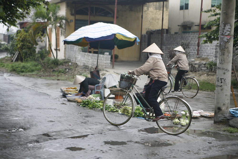 March 12th 2007. .Vietnamese people cycle on the road between Hanoi and Ha Long.