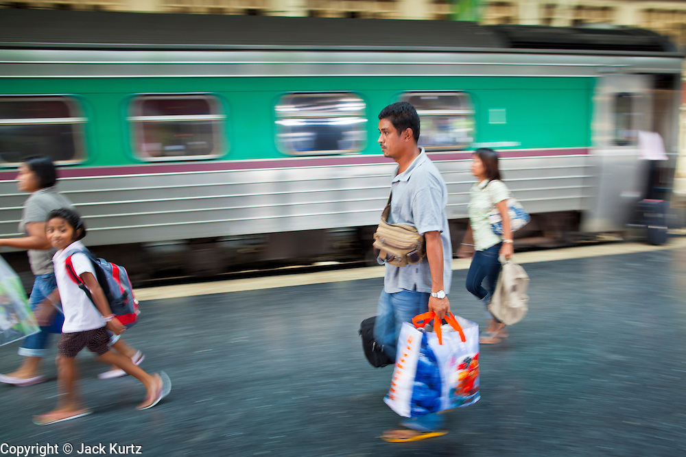 11 JULY 2011 - BANGKOK, THAILAND:  Passengers run to a train in Hua Lamphong station in Bangkok. Hua Lamphong Grand Central Railway Station, officially known as the Bangkok Grand Central Terminal Railway Station, is the main railway station in Bangkok, Thailand. It is located in the center of the city in Pathum Wan District, and is operated by the State Railway of Thailand. The station was opened on 25 June 1916, after six years' construction. The station was built in an Italian Neo-Renaissance style, with decorated wooden roofs and stained glass windows. The architecture is attributed to Turin-born Mario Tamagno, who, with countryman Annibale Rigotti made a mark on early 20th century public building in Bangkok. The pair also designed Bang Khun Prom Palace (1906), Ananda Samakhom Throne Hall in The Royal Plaza (1907-15) and Suan Kularb Residential Hall and Throne Hall in Dusit Garden, among other buildings..There are 14 platforms and 26 ticket booths. Hua Lamphong serves over 130 trains and approximately 60,000 passengers each day. Thailand has the most advanced rail system in Southeast Asia and trains from Hua Lamphong serve all corners of the Kingdom.        PHOTO BY JACK KURTZ
